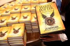 A store assistant holds copies of the book of the play of Harry Potter and the Cursed Child parts One and Two at a bookstore in London, Britain July 31, 2016. REUTERS/Neil Hall
