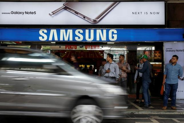 People stand near a Samsung Galaxy Note 5 advertisement at a mall in Jakarta, Indonesia, February 22, 2016. REUTERS/Beawiharta