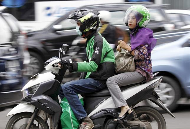 A woman rides on the back of a motorbike, part of the Go-Jek ride-hailing service, on a busy street in central Jakarta, Indonesia December 18, 2015. Indonesia's president publicly rebuked one of his cabinet ministers on Friday for a clampdown on ride-hailing services such as Uber and Go-Jek, which triggered outrage on social media in a country where public transport options are limited.  REUTERS/Garry Lotulung - RTX1Z7R3