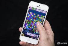 """Женщина играет в Candy Crush на iPhone в Нью-Йорке 18 февраля 2014 года. Квартальная выручка Activision Blizzard Inc выросла на 50,4 процента благодаря успеху нового многопользовательского шутера """"Overwatch"""" и покупке создателя хита """"Candy Crush"""" - компании King Digital. REUTERS/Carlo Allegri"""
