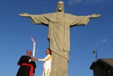 A chama subiu o Cristo Redentor e chegou às mãos do cardeal-arcebispo do Rio, dom Orani Tempesta. Ele acendeu a tocha que estava nas mãos da ex-jogadora de vôlei Isabel. 5/8/2016. REUTERS/Pilar Olivares