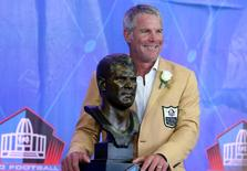 Aug 6, 2016; Canton, OH, USA; Former Green Bay quarterback Brett Favre stands with his bust during the 2016 NFL Hall of Fame enshrinement at Tom Benson Hall of Fame Stadium. Mandatory Credit: Aaron Doster-USA TODAY Sports