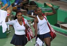 2016 Rio Olympics - Tennis - Preliminary - Women's Doubles First Round - Olympic Tennis Centre - Rio de Janeiro, Brazil - 07/08/2016. Serena Williams (USA) of USA and Venus Williams (USA) of USA leave after losing their match against Lucie Safarova (CZE) of Czech Republic and Barbora Strycova (CZE) of Czech Republic.  REUTERS/Toby Melville