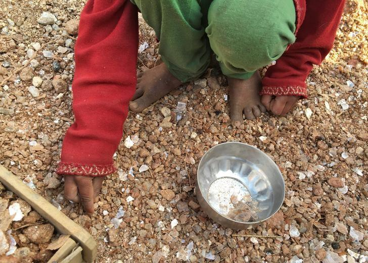 A five-year-old  girl collects mica flakes from an open cast illegal mica mine in Giridih district in the eastern state of Jharkhand, India, January 22, 2016. REUTERS/Nita Bhalla/Files