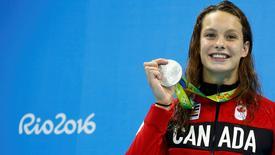 La canadiense Penelope Oleksiak celebra con su medalla de plata obtenida en los 100 metros mariposa femenino en los Juegos Olímpicos de Río, ago 7, 2016. La canadiense Penelope Oleksiak llegó a los Juegos Olímpicos con la esperanza de estar en una final y ganar experiencia de cara a  Tokio 2020. Pero tras solamente un par de días de competencia, la nadadora de 16 años tiene dos medallas y un teléfono inteligente con problemas de datos.         REUTERS/David Gray  IMAGEN SOLO PARA USO EDITORIAL