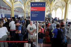 Passengers wait in line to check in after Delta Air Lines computer systems crashed leaving passengers stranded at airports around the globe as flights were grounded at Ronald Reagan Washington National Airport in Washington, U.S., August 8, 2016.      REUTERS/Joshua Roberts