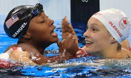 Simone Manuel and Penelope Oleksiak celebrate winning joint gold medals and also jointly breaking an Olympic record.  REUTERS/Dominic Ebenbichler