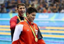 Joseph Schooling of Singapore is congratulated by Michael Phelps as they leave the podium.   REUTERS/Stefan Wermuth