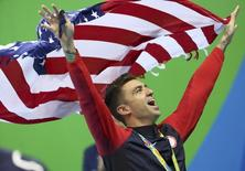 2016 Rio Olympics - Swimming - Victory Ceremony - Men's 50m Freestyle Victory Ceremony - Olympic Aquatics Stadium - Rio de Janeiro, Brazil - 12/08/2016. Anthony Ervin (USA) of USA celebrates with his gold medal while holding his national flag.      REUTERS/Stefan Wermuth