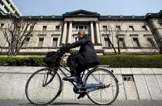 A man rides a bicycle past the Bank of Japan (BOJ) building in Tokyo March 18, 2009. REUTERS/Yuriko Nakao/File Photo