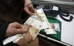 Продавец получает деньги от покупателя в магазине обуви в Красноярске. Реальная заработная плата в РФ в июле 2016 года сократилась на 5,5  процента к предыдущему месяцу и выросла на 0,6 процента к июлю 2015 года, составив в номинальном выражении 36.525 рублей, сообщилРосстат. REUTERS/Ilya Naymushin