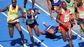 Mo Farah of Britain runs as Mead Hassan of USA falls after they nealy collided.  REUTERS/Dominic Ebenbichler