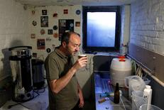 Pascal Screve, plumber and member of the Belgian Homebrewers association, inspects his own beer in the basement of his house in Brussels, Belgium, August 3, 2016. Picture taken August 3, 2016.   REUTERS/Francois Lenoir