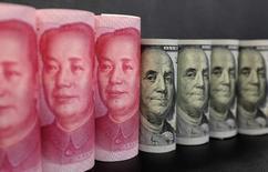 Банкноты достоинством $100 и 100 юаней на иллюстрации, сделанной в Пекине 21 января 2016 года. Китайские банки, столкнувшиеся с большим количеством проблемных кредитов, как ожидается, продемонстрируют ослабление показателей капитализации в финансовой отчетности за первое полугодие, усиливая вероятность того, что правительству придется влить более $100 миллиардов в финансовую систему для их поддержки, говорят аналитики. REUTERS/Jason Lee/Illustration/File Photo
