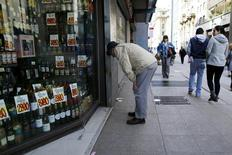 Una persona mira los precios de los productos desde fuera de una tienda en el centro de Santiago. 26 de agosto de 2016. La actividad económica en Chile habría crecido un 1,2 por ciento en julio, luego de que decepcionantes cifras de manufacturas y del sector minero limitaron el impulso de los rubros vinculados al consumo interno, mostró el martes un sondeo de Reuters. REUTERS/Ivan Alvarado