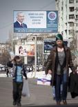 Прохожие на фоне предвыборного плаката с изображением президента Узбекистана Ислама Каримова в Ташкенте 21 марта 2015 года. Младшая дочь президента Узбекистана сообщила в среду, что тот поправляется после кровоизлияния в мозг на прошлой неделе, а диктор государственного ТВ зачитал речь бессменного лидера к юбилею независимости. REUTERS/Stringer