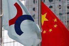 Флаги Гонконгской фондовой биржи (слева) и КНР у здания биржи в Гонконге 7 июня 2016 года. Китайские фондовые индексы незначительно повысились к закрытию торгов пятницы благодаря восстановлению акций сектора недвижимости. REUTERS/Bobby Yip/File Photo