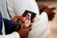 A nun from the members of Mother Teresa's order, the Missionaries of Charity, holds a prayer card during the unveiling an official canonization portrait of Mother Teresa at the John Paul II National Shrine in Washington, U.S., September 1, 2016. REUTERS/Gary Cameron