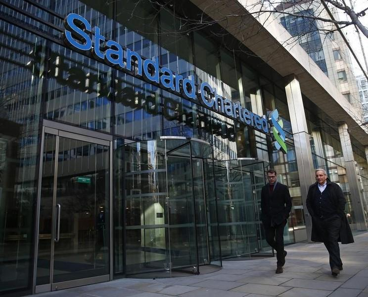People walk past the head office of Standard Chartered bank in the City of London February 27, 2015. REUTERS/Eddie Keogh