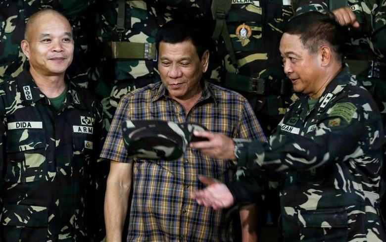A military officer escorts President Rodrigo Duterte during a visit at an army Camp Capinpin military camp in Tanay, Rizal in the Philippines August 24, 2016. REUTERS/Erik De Castro