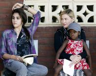 U.S. pop star Madonna looks at her daughter Lourdes (L) as she holds her adopted Malawian child Mercy James during a visit to Gumulira village, about 80 km (50 miles) from the Malawian capital Lilongwe, April 5, 2010        REUTERS/Mike Hutchings