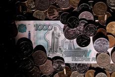 Рублевые монеты и купюра 7 июня 2016 года. Рубль дорожает утром четверга на фоне скачка нефтяных цен после данных о сильном падении запасов нефти в США по данным Американского института нефти. REUTERS/Maxim Zmeyev/Illustration
