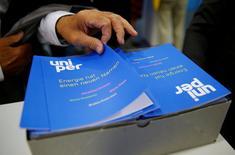 Un accionista de E.ON SE Climate and Renewables toma un folleto de Uniper SE, en Essen, Alemania. 8 de junio de 2016. Las acciones de Uniper comenzaron a cotizar el lunes por encima de 10 euros, en la parte superior de un rango proporcionado por los analistas, aunque se espera que la negociación sea volátil en su debut en bolsa tras escindirse de su matriz E.ON. REUTERS/Wolfgang Rattay/File Photo