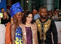 """Actress Lupita Nyong'o (L) and David Oyelow (R) stand with director Mira Nair as they arrives on the red carpet for the film """"Queen of Katwe"""" arrive on the red carpet for the film """"Queen of Katwe"""" during the 41st Toronto International Film Festival (TIFF), in Toronto, Canada, September 10, 2016.    REUTERS/Mark Blinch"""