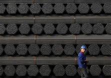 Un trabajador caminando junto a pilas de productos de acero en una planta en Tangshan, China. 3 de noviembre de 2015. La producción de acero crudo de China aumentó un 3 por ciento en agosto frente al mismo mes del año anterior, su sexto avance mensual consecutivo y la señal más reciente de que un rebote en los precios y una recuperación en la demanda han llevado a las acerías del país a reforzar su elaboración. REUTERS/Kim Kyung-Hoon/File Photo