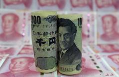 Банкноты 1000 иен на фоне купюр по 100 юаней. Пекин, 21 января 2016 года. Иена укрепилась на азиатской сессии в четверг, так как инвесторы находились в поисках тихой гавани на фоне ослабления рынка акций, хотя основные валютные пары практически не изменились в преддверии заседаний Банка Японии и Федрезерва на следующей неделе. REUTERS/Jason Lee