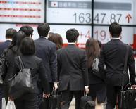 Люди проходят мимо экрана с котировками индекса Nikkei в Токио 13 апреля 2016 года. Японский индекс Nikkei отошёл от минимума трёх недель в пятницу после того, как связанные с Apple акции выросли благодаря успешным продажам нового iPhone 7 и покупкам акций банков после активной распродажи ранее на неделе. REUTERS/Toru Hanai