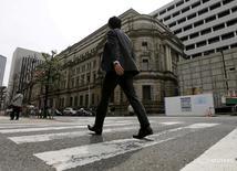 Бизнесмен идет мимо здания Банка Японии в Токио. Немногие японские компании считают, что агрессивный денежно-кредитный стимул Банка Японии поможет разогнать инфляцию до целевого показателя, показал опрос Рейтер. Фирмы говорили о негативном влиянии программы, которое оказалось сильнее положительных эффектов. REUTERS/Toru Hanai/File Photo - RTX2MMFJ