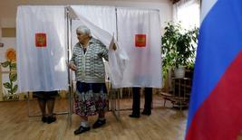 Женщина выходит из кабинки для голосования на избирательном участке в поселке Усть-Мана Красноярского края 18 сентября 2016. REUTERS/Ilya Naymushin