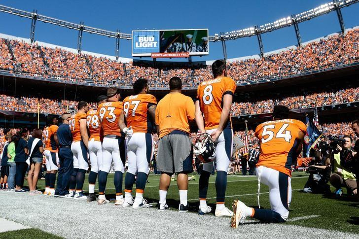 More kneeling football players, raised fists, in anthem