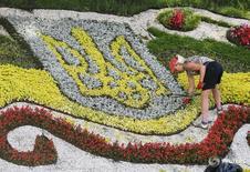Герб Украины из цветов в центре Киева 1 июля 2015 года. Украина, пережившая два предыдущих года благодаря финансовой поддержке Запада, планирует в 2017 году занять за рубежом 70,9 миллиарда гривен ($2,6 миллиарда), говорится в материалах проекта госбюджета. REUTERS/Gleb Garanich