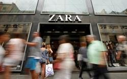 El grupo textil gallego Inditex, dueño de la marca Zara, registró en el primer semestre de su ejercicio fiscal 2016 un beneficio atribuible de 1.256 millones de euros, un aumento del 8 por ciento sobre el año anterior, dijo la empresa el miércoles. En la foto se ve a gente paseando por delante de una tienda de Zara en Barcelona el 20 de septiembre de 2016. REUTERS/Albert Gea