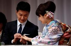 Japan's table tennis Olympian Ai Fukuhara (R) has her wedding ring placed on her finger by her husband Taiwan's table tennis Olympian Chiang Hung-chieh at a news conference to announce their marriage in Tokyo, Japan, September 21, 2016.  REUTERS/Toru Hanai