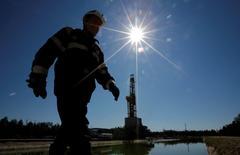Рабочий идет мимо буровой вышки на месторождении Приразломное рядом с Нефтеюганском. Бессмысленно говорить о заморозке или сокращении нефтедобычи ради поддержания цен на сырье, оставляя за бортом потенциал США со сланцевой нефтью, которые тут же займут освободившуюся нишу, считают эксперты, которые не верят в реализацию идеи и прогнозируют рост добычи в России в ближайшие годы. REUTERS/Sergei Karpukhin