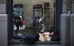 Un hombre duerme afuera de una sucursal bancaria en una oficina en el centro de Santiago, Chile. 11 de noviembre de 2014. El número de personas que vive en situación de pobreza en Chile disminuyó a un 11,7 por ciento en 2015 desde 2013, pese a la debilidad económica que ha marcado al país en los últimos años, según un informe bianual difundido el jueves por el gobierno. REUTERS/Ivan Alvarado
