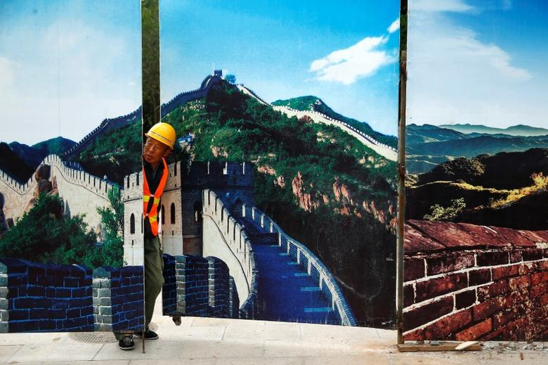 A worker looks through the fence of a construction site that is decorated with pictures of the Great Wall at Badaling, north of Beijing, China, September 1, 2016. REUTERS/Thomas Peter