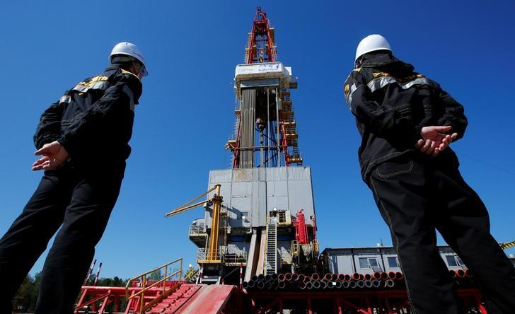 Workers look at a drilling rig at a well pad of the Rosneft-owned Prirazlomnoye oil field outside the West Siberian city of Nefteyugansk, Russia, August 4, 2016. REUTERS/Sergei Karpukhin/File Photo