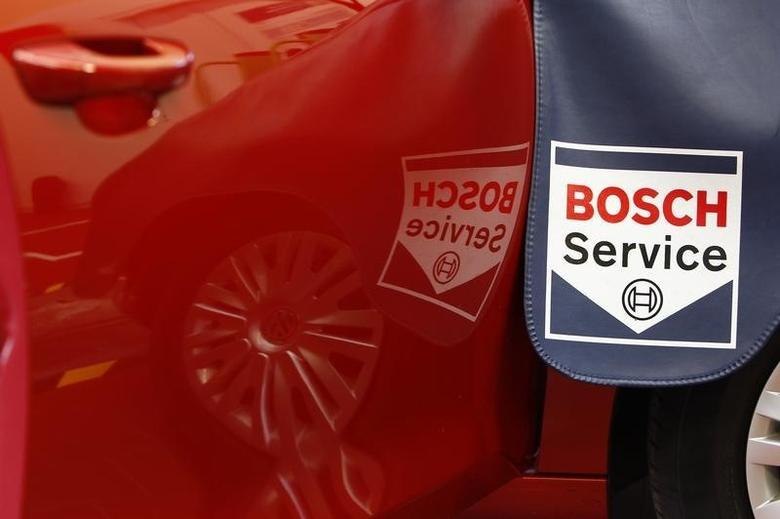 A Bosch Service sign is reflected in a car door while a product expert for diagnostics equipment of German auto parts supplier Robert Bosch analyses a car in a workout garage in Plochingen near Stuttgart April 15, 2013. REUTERS/Michaela Rehle