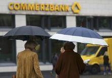 Personsa con paraguas caminan cerca de una sucursal de Commerzbank, en Fráncfort, Alemania. 30 de septiembre de 2016. Commerzbank dijo el viernes que buscaba sumar 2 millones de clientes minoristas y de pequeñas empresas en los próximos cuatro años, mientras impulsa una reestructuración que dejará a miles de personas sin trabajo. REUTERS/Kai Pfaffenbach