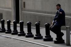 Трейдер отдыхает рядом с Нью-Йоркской фондовой биржей. Фондовые индексы США растут в пятницу, последний день третьего квартала, за счёт укрепления акций финансовых и технологических компаний.  REUTERS/Brendan McDermid