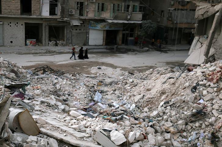 People walk past damaged buildings in the rebel held area of al-Kalaseh neighbourhood of Aleppo, Syria, September 29, 2016. REUTERS/Abdalrhman Ismail