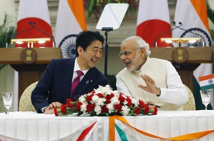 Japan's Prime Minister Shinzo Abe (L) and Narendra Modi shares a moment during a signing of agreement at Hyderabad House in New Delhi, December 12, 2015. REUTERS/Adnan Abidi/Files