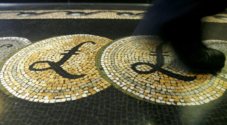 An employee is seen walking over a mosaic of pound sterling symbols set in the floor of the front hall of the Bank of England in London, Britain 25, 2008. REUTERS/Luke MacGregor/File Photo