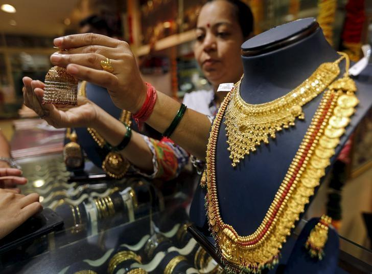 A saleswoman shows a gold earring to customers at a jewellery showroom in Mumbai, July 21, 2015. REUTERS/Shailesh Andrade/Files
