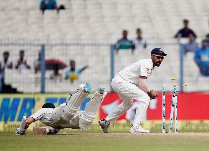 Cricket - India v New Zealand - Second Test cricket match - Eden Gardens, Kolkata, India - 02/10/2016. India's Shikhar Dhawan (R) attempts unsuccessfully to run out New Zealand's Bradley-John Watling. REUTERS/Rupak De Chowdhuri