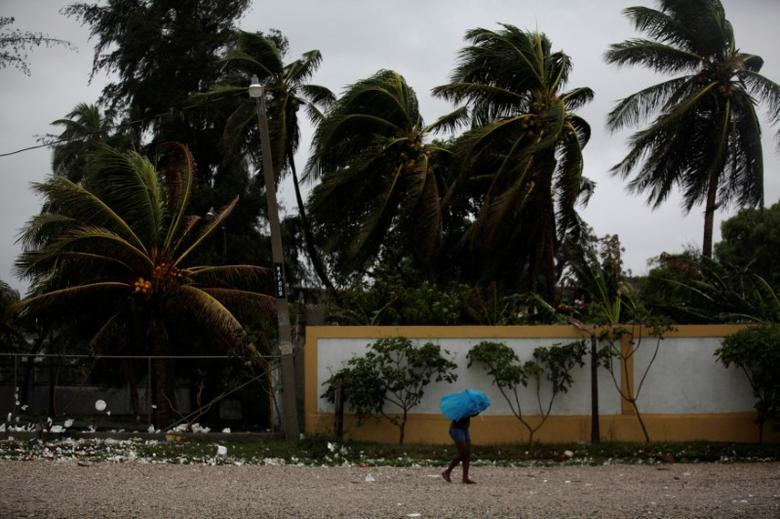 A woman protects herself from rain with an umbrella ahead of Hurricane Matthew in Les Cayes, Haiti, October 3, 2016. REUTERS/Andres Martinez Casares